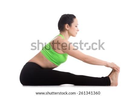 athletic beautiful girl does yoga exercises seated