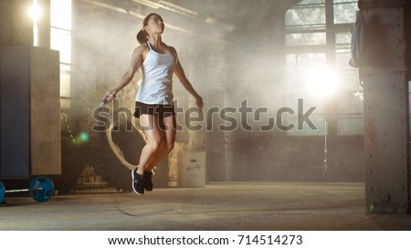 Stock Photo Athletic Beautiful Woman Exercises with Jump / Skipping Rope in a Gym. She's Covered in Sweat from Her Intense Fitness Training.
