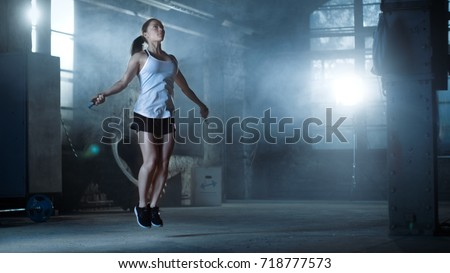 Athletic Beautiful Woman Exercises with Jump / Skipping Rope in a Gym. She's Covered in Sweat from Her Intense Fitness Training. Dark atmosphere.