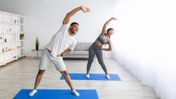 Athletic black couple bending aside, doing exercises at home, banner design with free space. African American guy and his lovely girlfriend having domestic training, working out together indoors