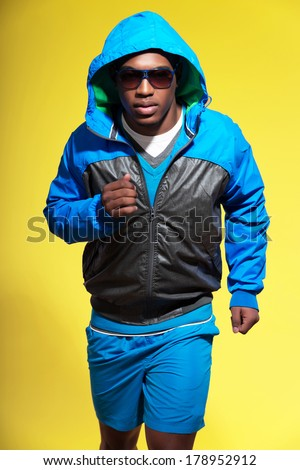Athletic black man in sportswear fashion. Runner with hoody jacket and sunglasses. Intense colors. Studio shot against yellow.