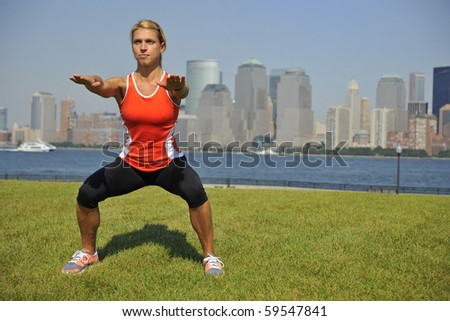 Athletic blond woman doing squatting exercise in sunny park in front of urban skyline.