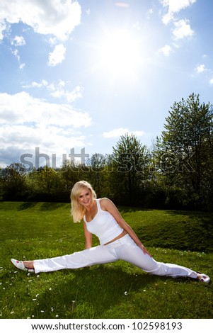 Athletic blonde woman dressed in a fresh white outfit stretching and doing the splits with her legs on a green lawn in a fitness concept