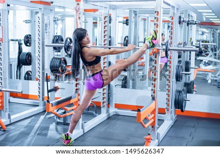 Athletic brunette doing the splits in the gym. Beautiful bodybuilder woman shows amazing stretching. The girl is losing weight by the summer, preparing a figure for the bikini season.