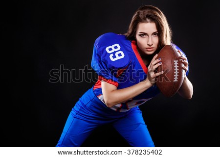 athletic brunette posing as american football girl on black background. Beautiful young woman wearing American football top holding ball. studio photo of american football woman
