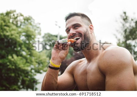 Athletic build man eating energy bar #691718512