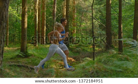 Athletic Caucasian man and his sporty girlfriend jog along the sunlit forest trail on a warm spring day. Focused fit training partners jogging together and preparing for a trail running marathon. #1372184951