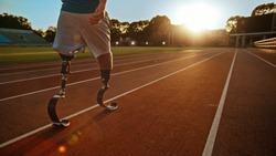 Athletic Disabled Fit Man with Prosthetic Running Blades is Walking During a Training on an Outdoor Stadium on a Sunny Afternoon. Amputee Runner Preparing for a Run. Motivational Sports Shot.