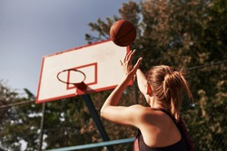 Athletic female basketball player throwing a ball up to the net.