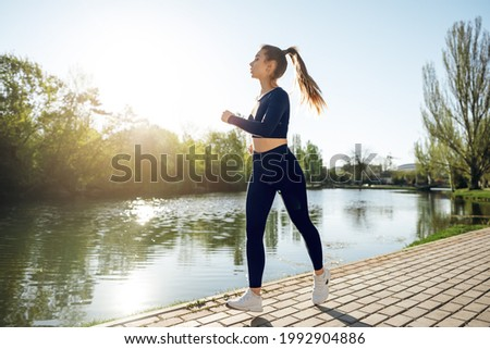 Athletic fit young woman jogging early in the morning in park