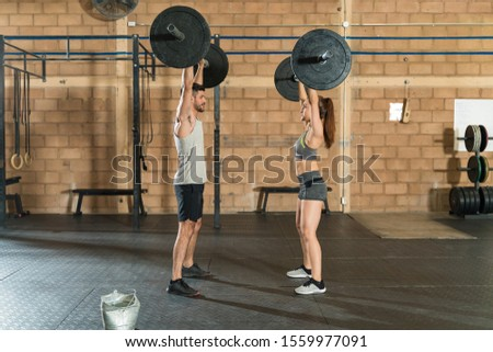 Athletic friends cross training while doing some weightlifting at health club