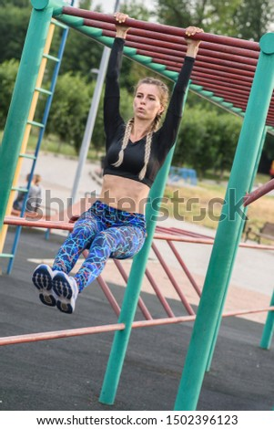 athletic girl doing exercises on the abs on the playground