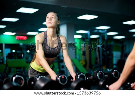 athletic girl is going to take dumbbells from a dumbbell row in the gym