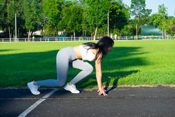 athletic girl jogging at stadium . low start. a head start. fir girl at football field