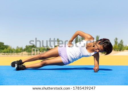 Athletic girl strengthening her abdominal area outdoors on a sunny day. Space for text. Concept of sport and healthy life.