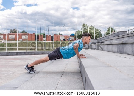 Athletic guy, in summer city push-ups from stairs, fitness workout, morning workout outdoors. Sportswear Sneakers Shorts. Active lifestyle of youth