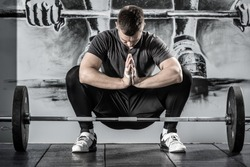 Athletic guy sits in the squat above a barbell in the gym on the wall with picture background. He holds his hands together and looks on them. Man wears sportswear with the white sneakers. Horizontal.