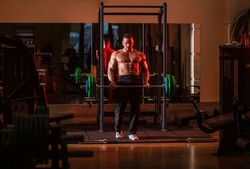 Athletic guy standing with barbell, workout in gym. Muscular man workout with barbell at gym. Bodybuilder athletic man with six pack, perfect abs, shoulders, biceps, triceps, chest. Barbells workout.