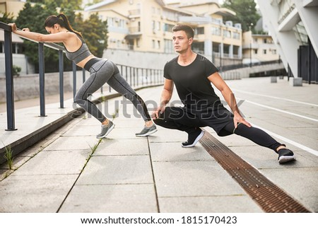 Athletic handsome man and slim pretty woman are spending day by exercising in open air in city Foto stock ©