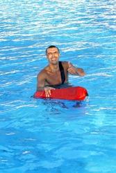Athletic lifeguard posing in swimming pool