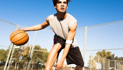 Athletic male basketball player in action outdoors. Man dribbling the ball at the court.