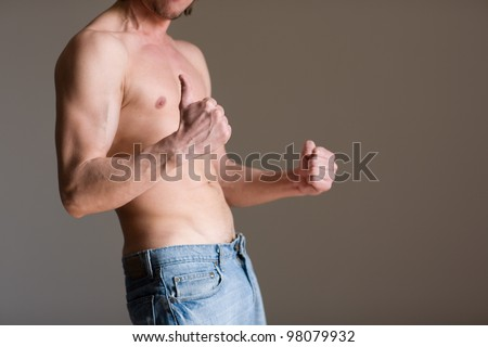 Athletic male body against a wall.