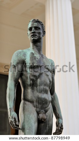 athletic male bronze statue with a longing stare in front of greek columns