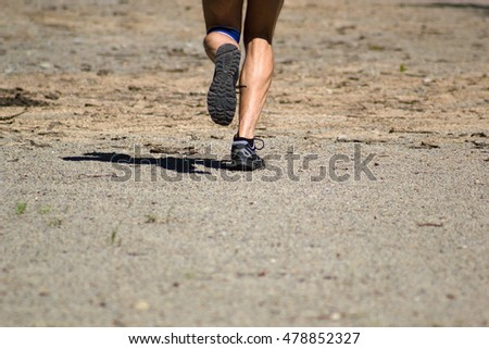 Athletic male feet running on dirt road #478852327