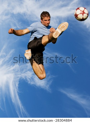 Athletic male high in the air kicking a soccer ball