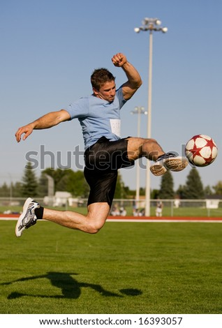 Athletic male in the air kicking a soccer ball
