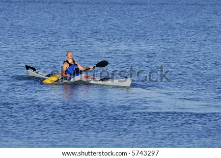 Athletic male kayaker emerges on the surface after paddle float assisted re-entry and roll.