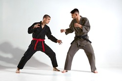 Athletic males in kimono fighting during kudo workout on white studio background with copy space, martial arts concept