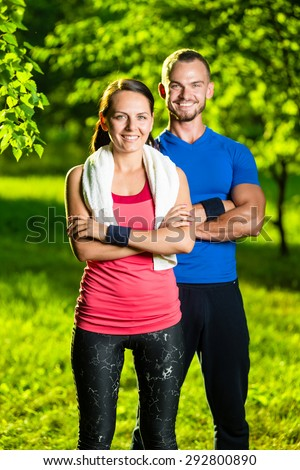 Athletic man and woman after fitness exercise. Beautiful young couple in sports clothing after outdoor exercises. White towel.