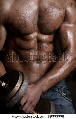 Athletic man body parts. Abdominal muscles. With dumbbell.