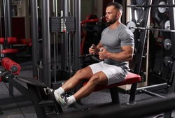 Athletic man doing back workout at cable row machine