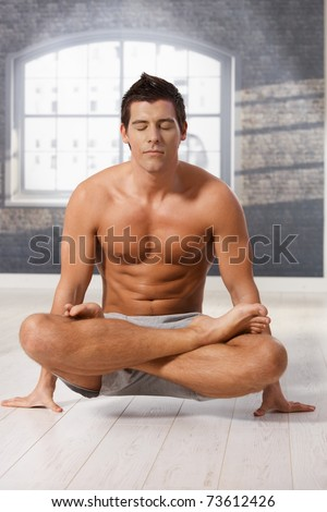 Athletic man doing exercise in lotus posture on floor with eyes closed.?