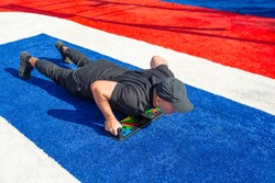 Athletic man doing push-ups on a push-up board at the sports field in the city park.