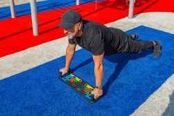 Athletic man doing push-ups wide grip on a push-up board at the sports field in the city park.