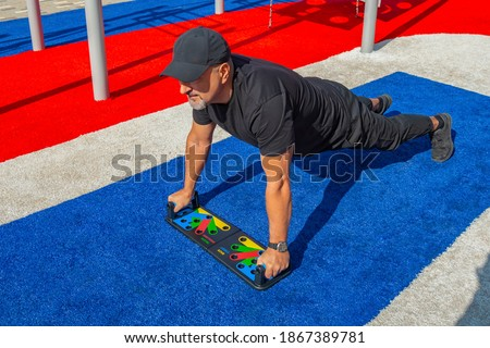 Photo of  Athletic man doing push-ups wide grip on a push-up board at the sports field in the city park.