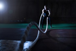 Athletic man doing some cross-training exercises with a rope in gym