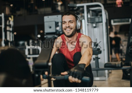 Athletic man doing workouts on a back with power exercise machine in a gym club