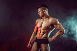 Athletic man flexing muscles in studio on dark background with smoke. Strong bodybuilder with perfect abs.