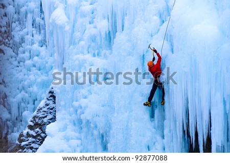 Athletic man in red coat with orange helmet and gold ice tools climbing a large blue wall of ice in the Uncomphagre Gorge