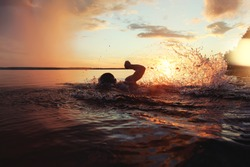 Athletic man is trained to swim in a lake at sunset. It flies a lot of water splashing. Vintage color