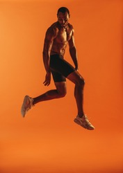 Athletic man jumping in air while working out on orange background. Monochrome fitness portrait of muscular athlete doing workout.