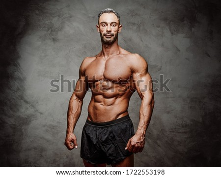 Athletic man posing for a photoshoot isolated on the grey concrete background, wearing sportive shorts, looking serious Stock photo ©