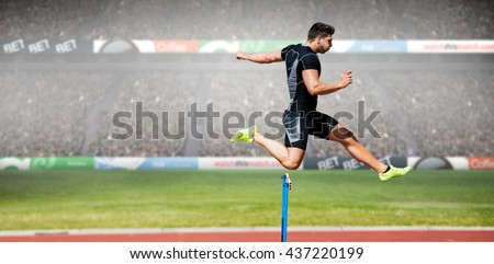 Athletic man practicing show jumping against view of a stadium Сток-фото ©