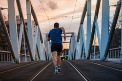 Athletic man practicing sport outdoors rear view running fast along bridge. Self overcome conquering obstacles and win. Healthy lifestyle concept. Workout jogging activity.