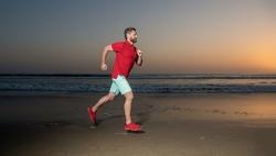 athletic man runner running on sunset summer beach, stamina