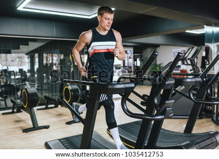 Athletic man running in a modern gym on a treadmill doing cardio exercises. Young handsome fit man running on treadmill in the fitness club. Sport, fitness, healthy life and people concept.
